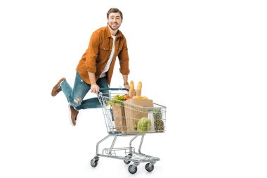 positive man jumping and carrying shopping trolley with products in paper bags isolated on white