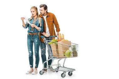 shocked couple with trolley full of products in paper bags looking at shopping check isolated on white