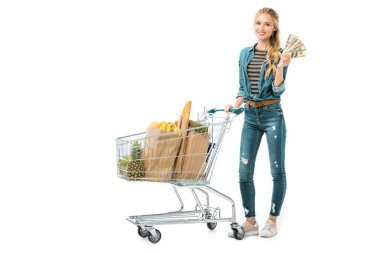 smiling girl standing near shopping trolley with products and showing cash money isolated on white