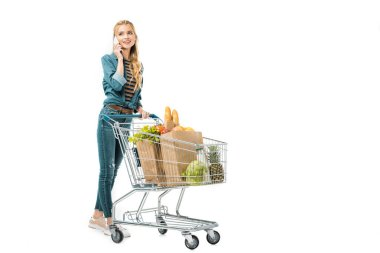 beautiful woman talking on smartphone and carrying shopping trolley with products isolated on white