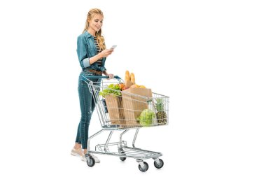 smiling woman using smartphone and carrying shopping trolley with products isolated on white