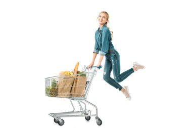 Happy young woman jumping near shopping trolley cart with products in paper bags isolated on white stock vector