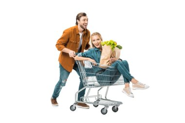 laughing man carrying shopping trolley with girlfriend while she holding paper bags with food isolated on white