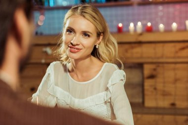 Selective focus of smiling beautiful woman having date with boyfriend at restaurant stock vector