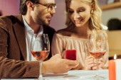 Fotografie partial view of man proposing to girlfriend at table with wine glasses in restaurant