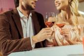 částečný pohled pár cinkání do sklenky na víno během dne u stolu v kavárně
