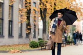 handsome stylish man in coat and scarf with umbrella walking by autumnal street