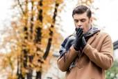Photo bottom view of stylish man in coat freezing on autumnal street