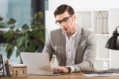 Photo handsome stylish businessman working with laptop at office