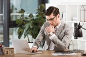 Photo handsome focused businessman working with laptop at office