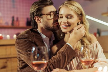 Side view of young man in jacket kissing beautiful girlfriend during romantic dinner at restaurant stock vector