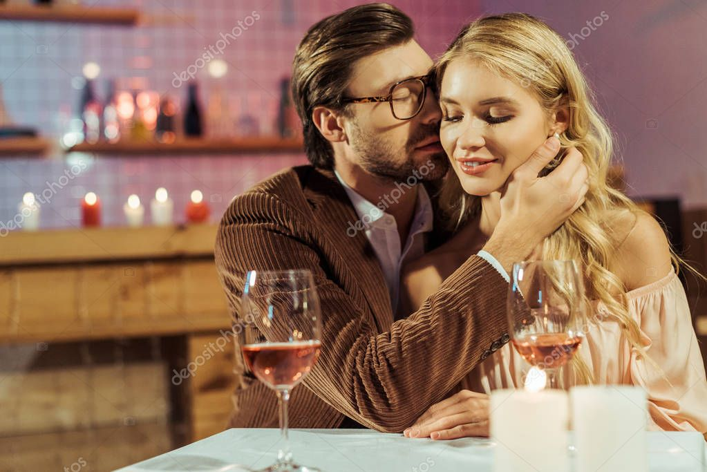 Man in jacket kissing beautiful girlfriend during romantic dinner at restaurant stock vector