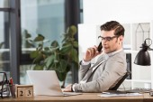 Fotografie successful confident businessman talking by phone at workplace in office