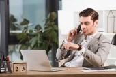 Fotografie gut aussehend zuversichtlich Geschäftsmann Gespräch per Telefon am Arbeitsplatz im Büro