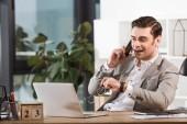 hezký šťastný podnikatel mluvil telefonicky na pracovišti v kanceláři a při pohledu na obrazovku u notebooku