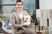 hezký šťastný podnikatel sedí na stole na pracovišti a držení tabletu s ebay stránky na obrazovce