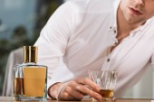 Photo cropped shot of drunk businessman holding glass of whiskey at office