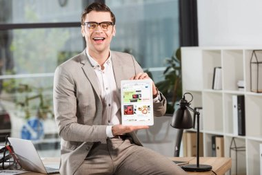 handsome happy businessman sitting on desk at workplace and holding tablet with ebay website on screen