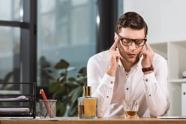 overworked businessman with glass of whiskey suffering from headache at office