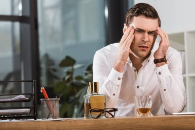 depressed businessman with glass of whiskey suffering from headache at office