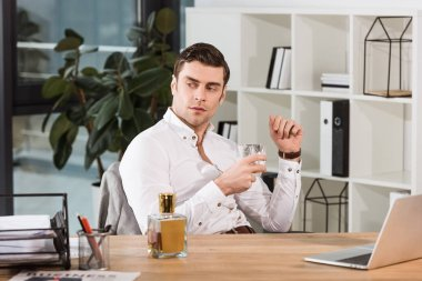 handsome serious businessman with glass of whiskey sitting at workplace in office