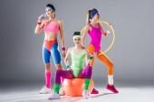 sportovní mladé ženy s obručí, činky, fit ball a láhev vody na grey