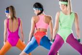 zadní pohled na sportovní dívek školení na aerobik cvičení izolovaných na šedá