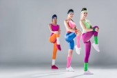 Fotografie beautiful young sportswomen exercising together and smiling at camera on grey