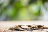 close-up view of pile of coins on tabletop and blurred background