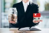 oříznuté záběr podnikatelka drží sklo jar s mincí a malý domek model