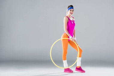 beautiful sporty girl standing with hula hoop and smiling at camera on grey