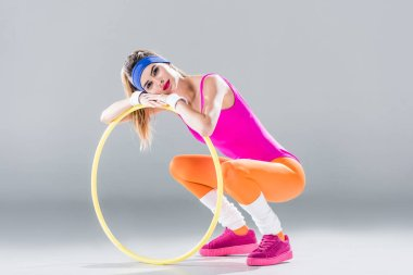 attractive young sportswoman leaning at hula hoop and smiling at camera on grey