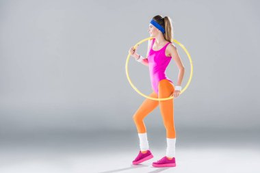 full length view of smiling sporty woman training with hula hoop on grey