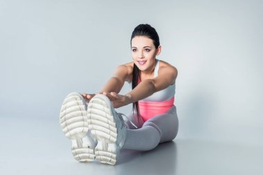 Smiling sporty girl stretching and looking away on grey stock vector
