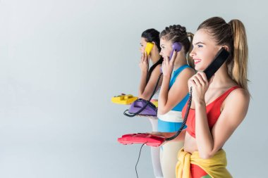 side view of smiling sporty girls talking by rotary phones and looking away isolated on grey