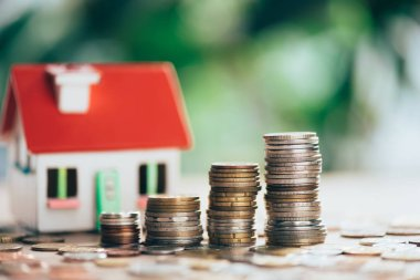 close-up view of stacked coins and house model, savings concept