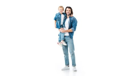 Father holding his pretty son and looking at camera isolated on white
