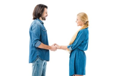Amazing couple holding hands and amorously looking at each other isolated on white