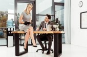 Fotografie lawyer looking at beautiful female colleague on table in office, office romance concept