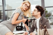 businesswoman holding colleagues tie while flirting at workplace in office