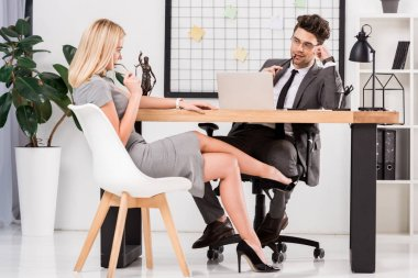 young businesswoman flirting with business colleague at workplace with laptop in office