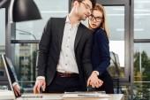 Fotografie mladí podnikatelé drží za ruce při flirtování na pracovišti, úřad romance koncept