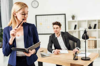 selective focus of young businessman looking at beautiful with folder in office