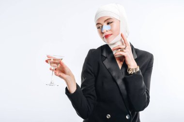 Stylish smiling  woman with bandages over head after plastic surgery holding glass with cocktail isolated on white stock vector