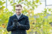 Fotografie smiling man typing on smartphone with blurred tree