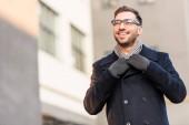 Fotografia uomo sorridente bello che tiene il colletto del cappotto con costruzione