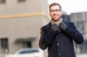 Fotografia uomo sorridente bello che tiene il colletto del cappotto il parcheggio
