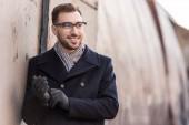 Fotografia uomo sorridente bello in piedi vicino al muro di metallo rustico