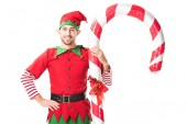 Photo smiling man in christmas elf costume with hand on hips standing near big candy cane isolated on white