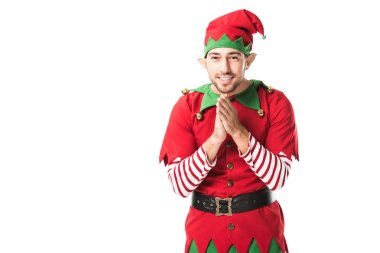 Smiling man in christmas elf costume looking at camera and rubbing hands in anticipation isolated on white stock vector